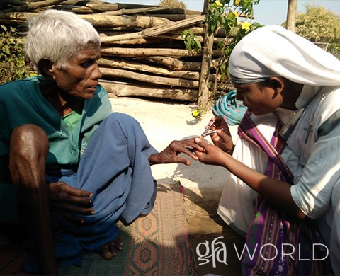 A Sister of Compassion trims the nails of a woman in need.