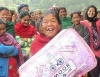 A 65-year-old lady joyfully receives a winter blanket.