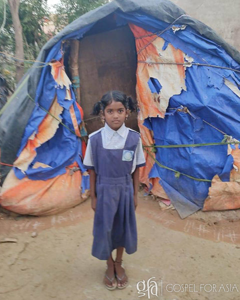 young Divena pictured in front of her tent where she and her brother lived alone