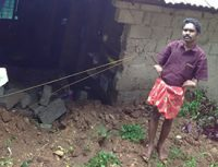Man stands beside hole in his house caused by a landslide.